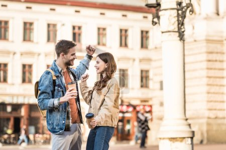 Photo for Excited boyfriend and girlfriend with disposable cups of coffee looking at each other and smiling in city - Royalty Free Image
