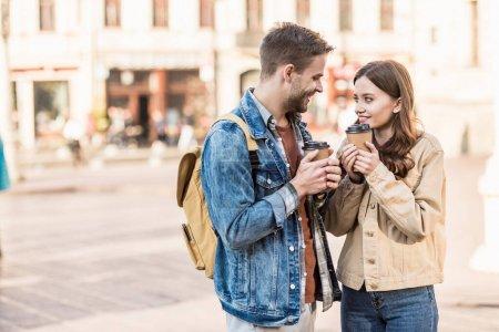 Foto de Hombre y chica sosteniendo tazas de café desechables con las manos apretadas, mirándose y sonriendo en la ciudad - Imagen libre de derechos