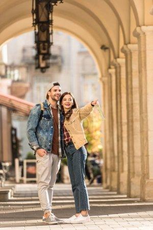 Photo pour Focus sélectif de petit ami et petite amie pointant avec le doigt et souriant dans la ville - image libre de droit