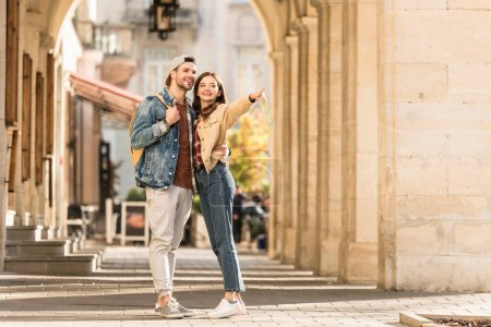 Selective focus of boyfriend hugging girlfriend pointing with finger and smiling in city