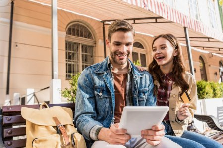Selective focus of couple smiling and holding credit card and digital tablet on bench in city