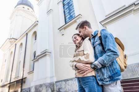 Photo for Low angle view of boyfriend and girlfriend hugging near building in city - Royalty Free Image