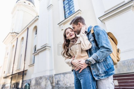 Low angle view of boyfriend and girlfriend hugging near building in city