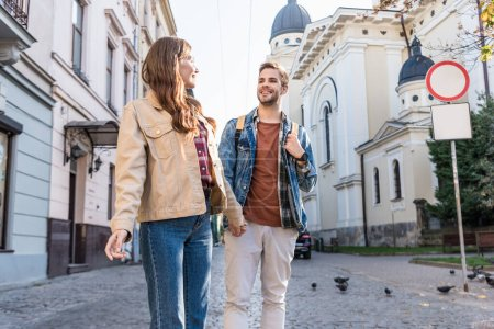 Selective focus of couple looking at each other and holding hands in city