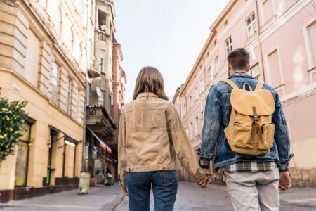 Photo for Back view of couple holding hands with backpack in city - Royalty Free Image