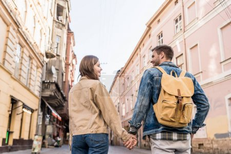 Photo for Back view of couple looking at each other and holding hands with backpack in city - Royalty Free Image