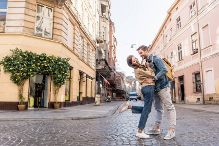 Selective focus of couple having fun and looking at each other in city