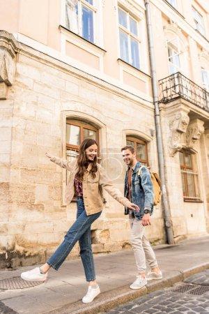 Photo pour Couple s'amuser en marchant sur le trottoir en ville - image libre de droit