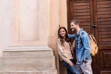 Petit ami et petite amie souriant près du mur en ville