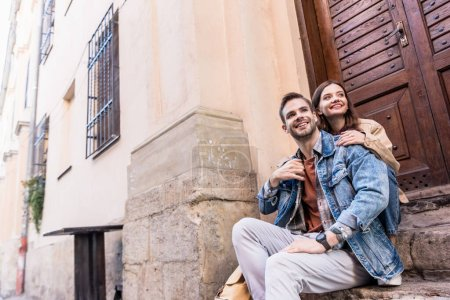 Photo for Low angle view of girlfriend hugging boyfriend and smiling on stairs in city - Royalty Free Image