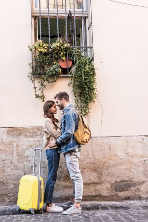 Photo for Couple with backpack and suitcase hugging near wall in city - Royalty Free Image