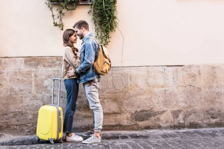 Couple with backpack and suitcase hugging near wall in city