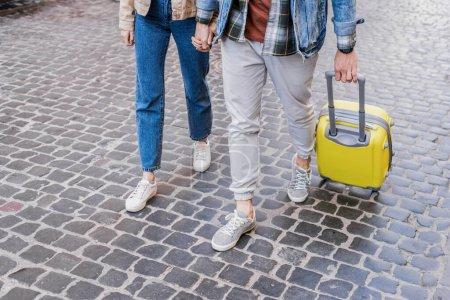Photo pour Vue croustillante d'un couple tenant les mains et voyageant avec sa valise - image libre de droit