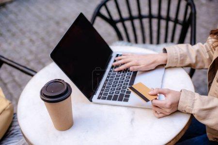 Photo pour Vue recadrée de la femme tenant la carte de crédit et utilisant un ordinateur portable dans le café - image libre de droit