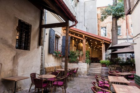 Photo for Cafe with terrace and wooden tables in city - Royalty Free Image