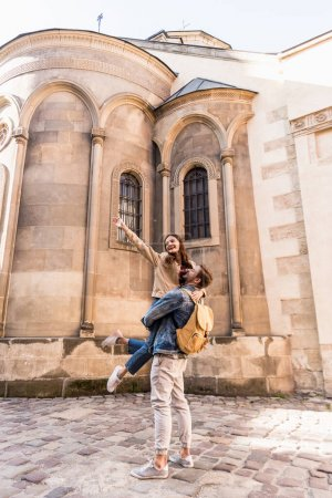 Photo for Boyfriend with backpack holding girlfriend with outstretched hand near building in city - Royalty Free Image