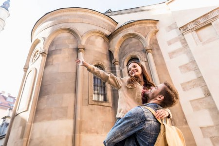 Photo pour Vue à angle bas d'un petit ami tenant sa petite amie la main tendue près d'un immeuble en ville - image libre de droit