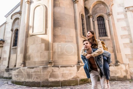 Excited man piggybacking girlfriend near building in city