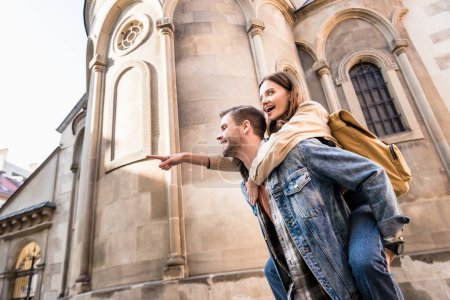 Low angle view of man piggybacking girlfriend pointing with finger near building in city