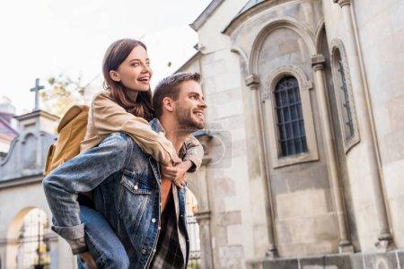 Photo pour Selective focus of man piggybacking petite amie près d'un immeuble en ville - image libre de droit