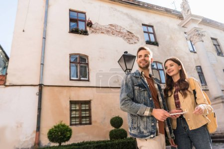 Low angle view of couple with digital tablet looking away and smiling in city