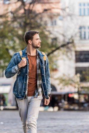 Photo pour Beau homme marchant avec son sac à dos et regardant loin en ville - image libre de droit
