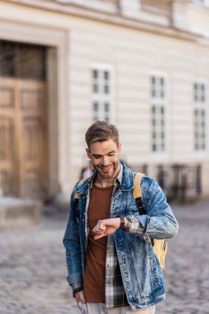 Photo pour Beau homme avec la main dans la poche souriant et regardant la montre-bracelet en ville - image libre de droit