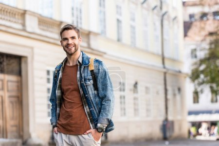 Photo for Handsome man with hands in pockets smiling in city - Royalty Free Image