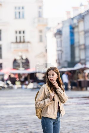Photo for Beautiful woman looking away with backpack in city - Royalty Free Image