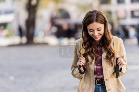 Beautiful woman smiling with backpack in city