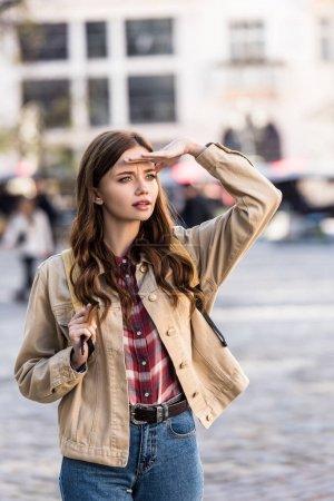 Foto de Mujer hermosa concentrada mirando hacia fuera con mochila en la ciudad - Imagen libre de derechos
