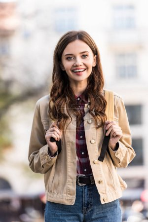 Photo for Attractive girl looking at camera and smiling with backpack in city - Royalty Free Image