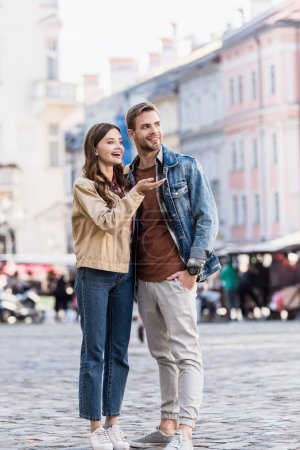 Photo for Boyfriend and girlfriend looking away and smiling in city - Royalty Free Image