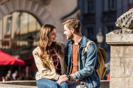 Photo for Happy girlfriend and boyfriend sitting together, looking at each other and smiling in city - Royalty Free Image