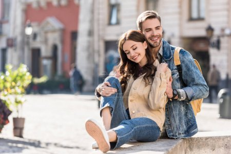 Selective focus of boyfriend hugging girl sitting on stone surface and smiling in city