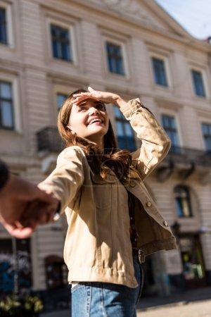 Foto de Vistas cruzadas novia y novio teniendo las manos y sonriendo en la ciudad. - Imagen libre de derechos