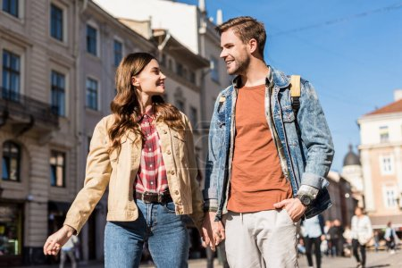 Girlfriend and boyfriend holding hands looking at each other and smiling in city