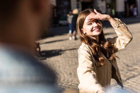 Photo pour Vue croustillante d'une fille souriante, couvrant son visage de la lumière du soleil et tenant la main d'un homme en ville - image libre de droit