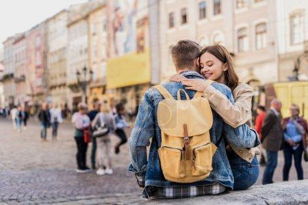 Photo pour Petit ami avec sac à dos et petite amie avec les yeux fermés étreignant et souriant en ville - image libre de droit