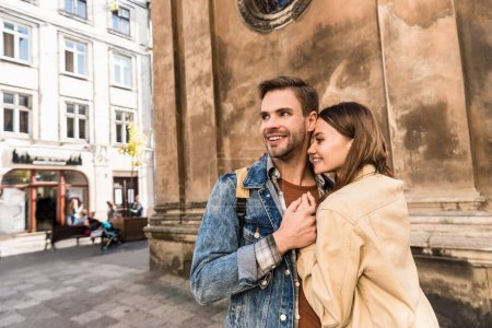 Photo for Selective focus of girlfriend and boyfriend looking away, holding hands and smiling near wall in city - Royalty Free Image