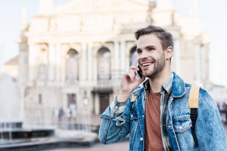 Photo for Handsome man smiling and talking on smartphone in city - Royalty Free Image