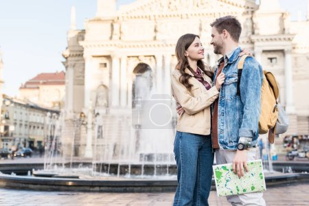 Couple looking at each other hugging with map near fountain in city