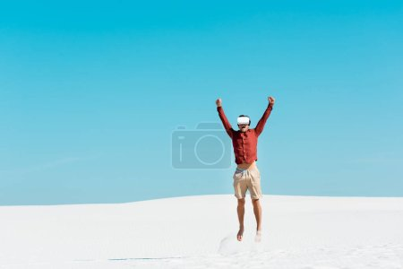 man on sandy beach in vr headset jumping against clear blue sky