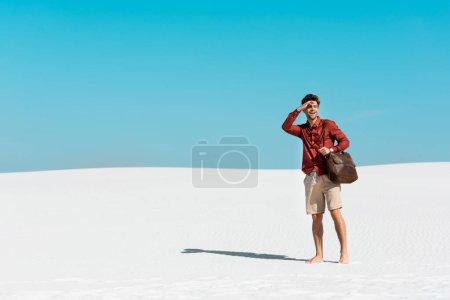 Photo pour Bel homme avec sac en cuir regardant loin sur la plage de sable contre ciel bleu clair - image libre de droit