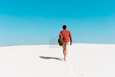 Photo pour Vue arrière de l'homme avec sac en cuir marchant sur la plage de sable contre un ciel bleu clair - image libre de droit