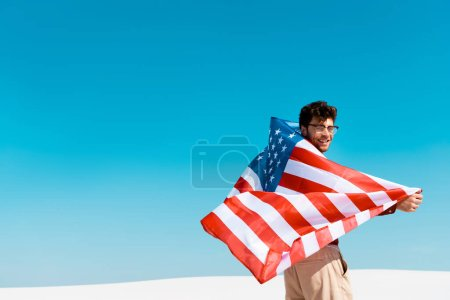 Photo pour Homme heureux avec drapeau américain sur la plage de sable venteux contre ciel bleu clair - image libre de droit