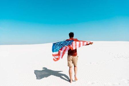 Photo pour Vue arrière de l'homme avec drapeau américain sur une plage de sable venteux contre un ciel bleu clair - image libre de droit