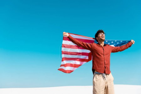happy man with american flag on windy sandy beach against clear blue sky
