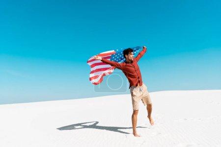 Photo pour Homme avec drapeau américain sur la plage de sable venteux contre ciel bleu clair - image libre de droit