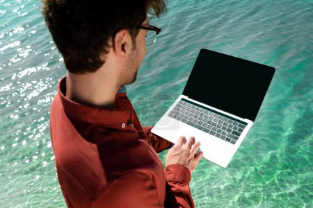 Photo for Handsome freelancer with laptop standing in turquoise water - Royalty Free Image